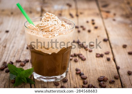 Ice coffee with whipped cream in a glass on the wooden table - stock photo