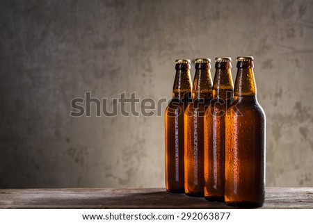 Ice cold beer bottles in a row over the grey concrete wall background - stock photo