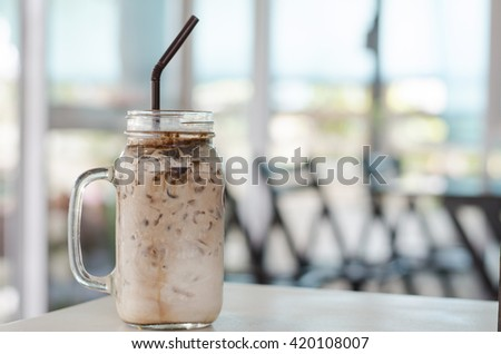 Ice cold chocolate milk in a bottle with blurred background in cafe. Sweet chocolate for healthy dessert. - stock photo