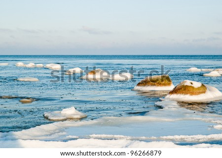 ice-covered stones along the shores of the Baltic Sea - stock photo