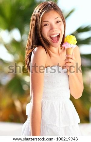Ice cream girl excited and happy eating ice cream cone on beach during summer vacation. Lovely sweet mixed race Asian Chinese / Caucasian young woman outside. - stock photo