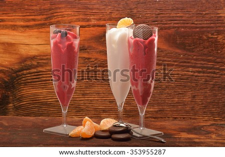 Ice cream, red sorbet and white sorbet on wooden background - stock photo