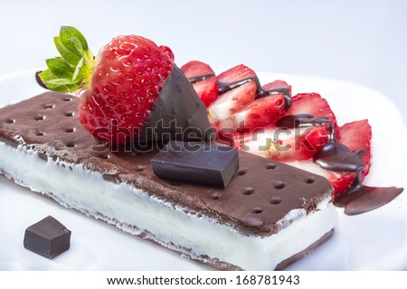 Ice cream sandwich served with chocolate dipped strawberry. - stock photo