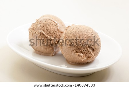 ice cream scoops on white plate close-up  against neutral background  - stock photo