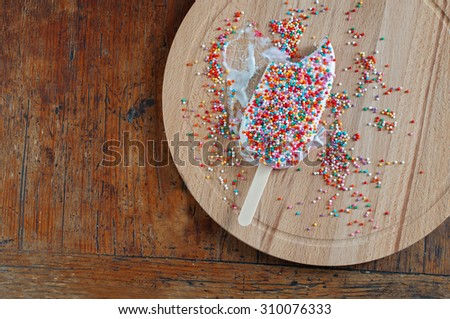 Ice Cream with Rainbow Sprinkles Topping on wooden background - stock photo
