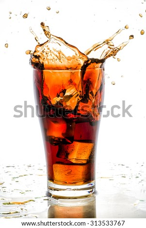 Ice cube droped in cola glass and cola splashing. - stock photo