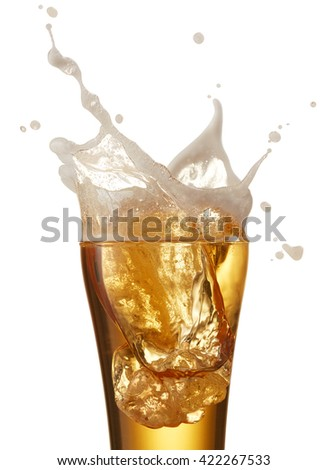 ice cube dropped into glass of beer creating splash - stock photo