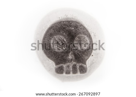 Ice Cube in the shape of a human skull melting on a white background - stock photo