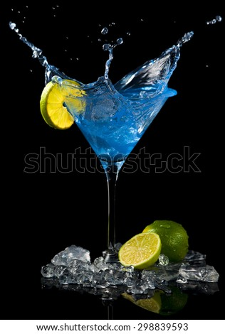 ice cube splashing in blue cocktail with lime slice, black background - stock photo