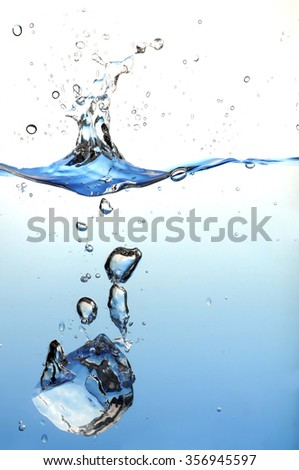 ice cube splashing in the water  - stock photo