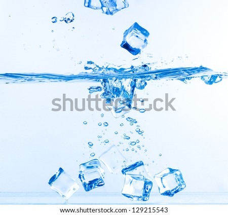 Ice Cubes Dropped into Water with Splash on white - stock photo