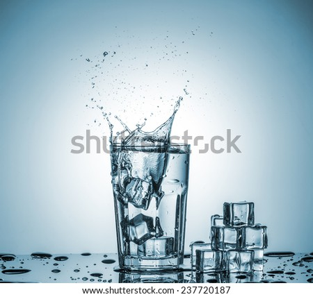 ice cubes falling into a glass of water and ice cubes, lying next, on blue background - stock photo