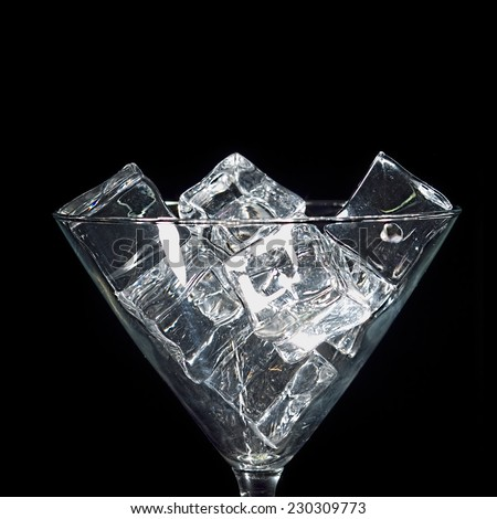 Ice cubes in glass against black background. - stock photo
