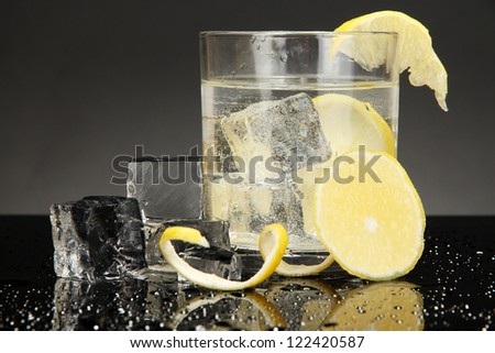 Ice cubes in glass with lemon isolated on black - stock photo