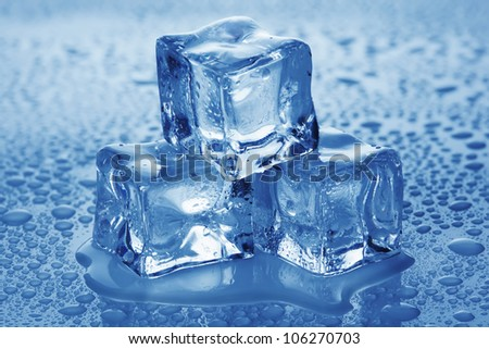 Ice cubes on the surface covered with water drops. - stock photo