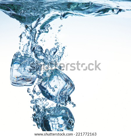 Ice cubes on white background poured in water - stock photo