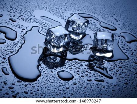 Ice cubes over dark background - stock photo