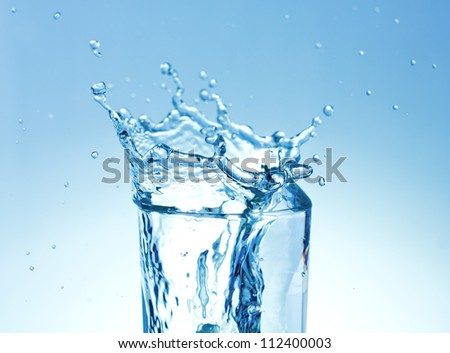 Ice cubes splashing into glass of water - stock photo