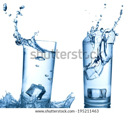 Ice cubes splashing into glass of water, isolated on white - stock photo