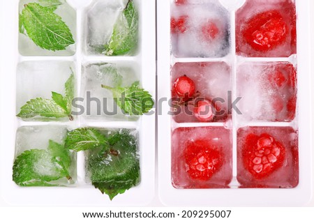 Ice cubes with forest berries, mint leaves in ice cube tray, close-up - stock photo