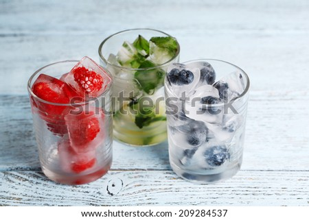 Ice cubes with mint leaves, raspberry and blueberry in glasses, on color wooden background - stock photo