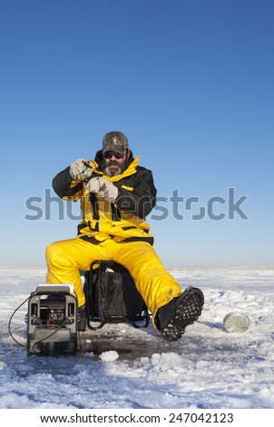 Ice fisher man with beard fighting a fish. - stock photo