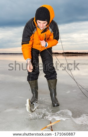 Ice fishing in the early morning. - stock photo