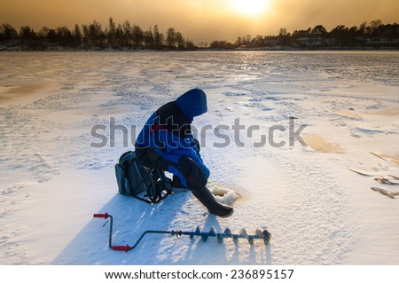 Ice fishing on thick ice with hand ice auger in front - stock photo