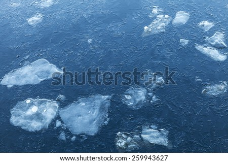 Ice fragments under thin layer of frozen river water. Dark blue natural background - stock photo