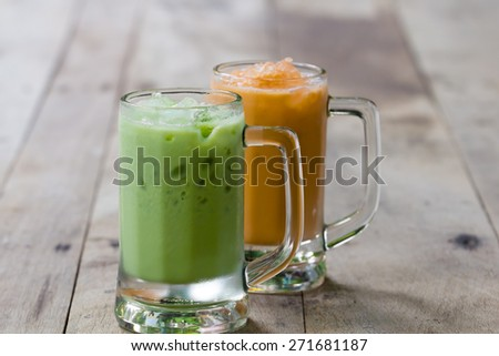Ice green tea and milk tea in glass place on wooden - stock photo
