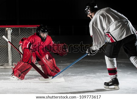 Ice hockey action shot with forward player and goalie. - stock photo