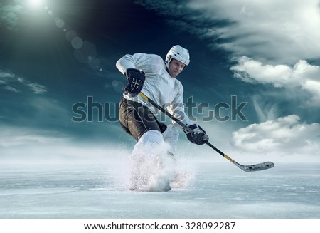 Ice hockey player in action outdoor around mountains - stock photo