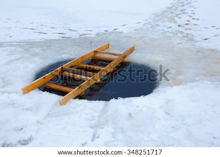 ice hole with a ladder. hole in the ice for winter swimming the river. ice hole equipped with a wooden ladder. ladder lies across the hole - stock photo