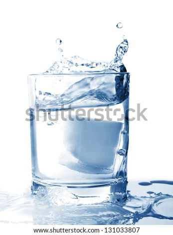 Ice in glass of water with splash on white background - stock photo
