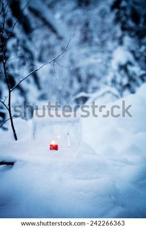 Ice lantern with red candle burning inside - stock photo