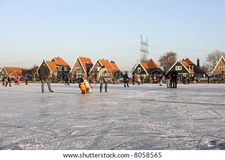 Ice skating in the countryside from the Netherlands with view on a dutch village - stock photo