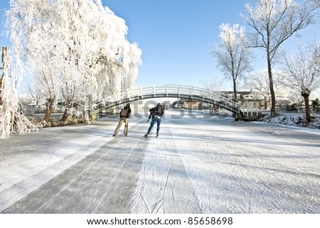 Ice skating in the countryside in winter in the Netherlands - stock photo