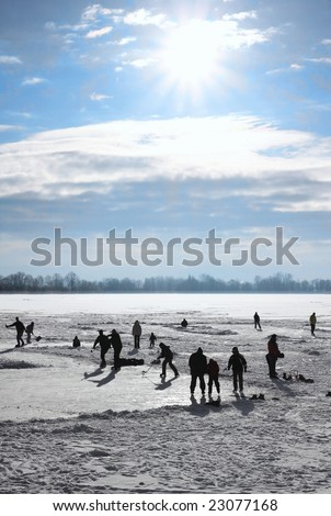 Ice-skating on frozen lake behind sunny of the day - stock photo