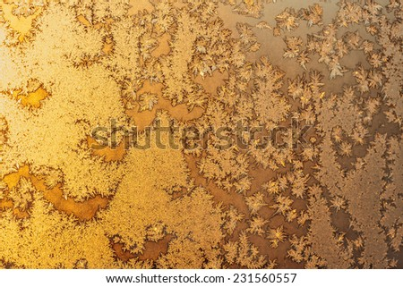 Ice snowflakes and frost pattern on frozen Christmas winter window. Colored in yellow or gold tone. Selective focus at center with blur edges of image - stock photo