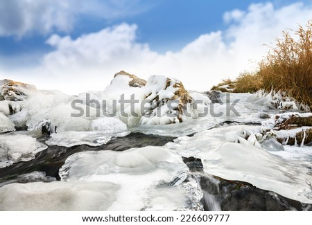 ice Water source. Winter creek against  blue sky. - stock photo