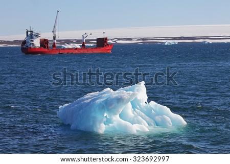 Iceberg and cargo ship  - stock photo