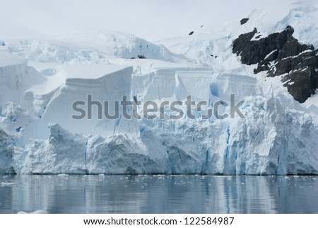 Iceberg breaks off from a glacier in the summer. - stock photo