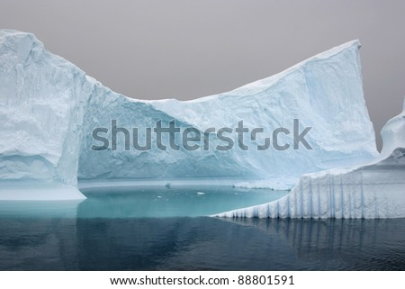 Iceberg floating in the sea, cloudy day - stock photo