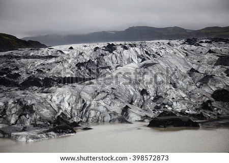 Iceberg on Iceland covered with ash from recent volcano eruption - stock photo