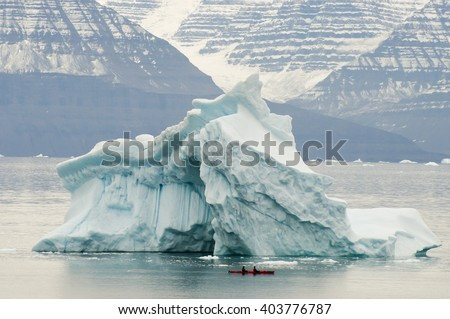 Iceberg with Kayak as Scale - Scoresby Sound - Greenland - stock photo