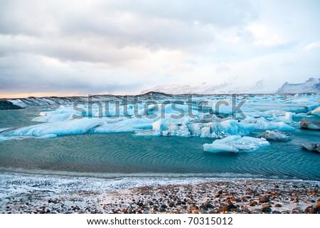 Icebergs drifting to sea in Jokulsarlon - Iceland - stock photo