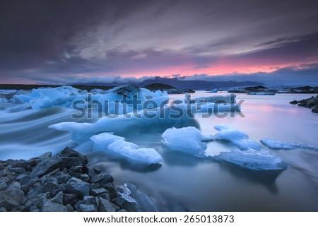 Icebergs floating in Jokulsarlon glacier lagoon lake at sunset. South Iceland/ Jokulsarlon Ice Waterfall - stock photo
