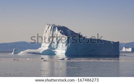Icebergs of Greenland under a bright sun of polar summer. Deep pure waters of  northen seas. - stock photo