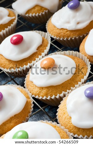 Iced buns on a tray with coloured sweet tops - stock photo