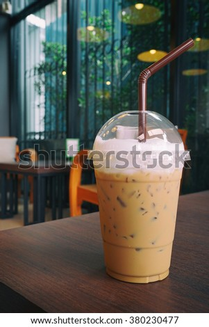 Iced coffee in Coffee shop  ,Iced coffee with straws in plastic cup on wooden background, Selective focus,Film simulation - stock photo